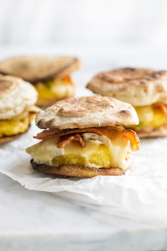 bacon brie breakfast sandwiches on parchment paper