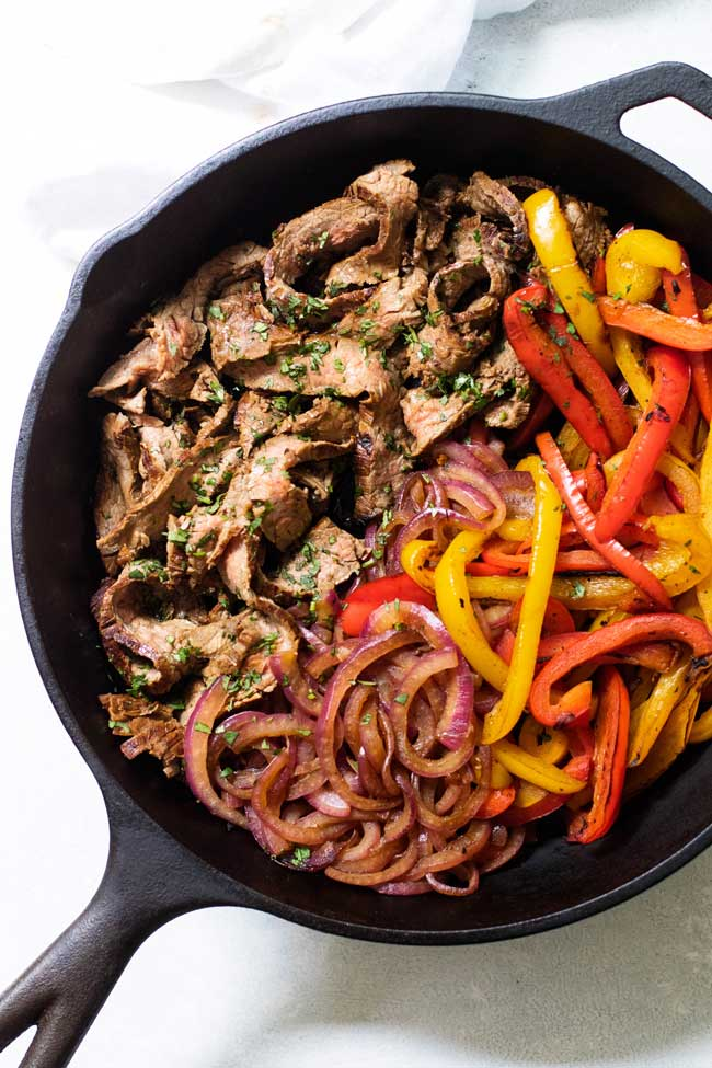 overhead shot of beef, peppers, and onions in a cast iron skillet