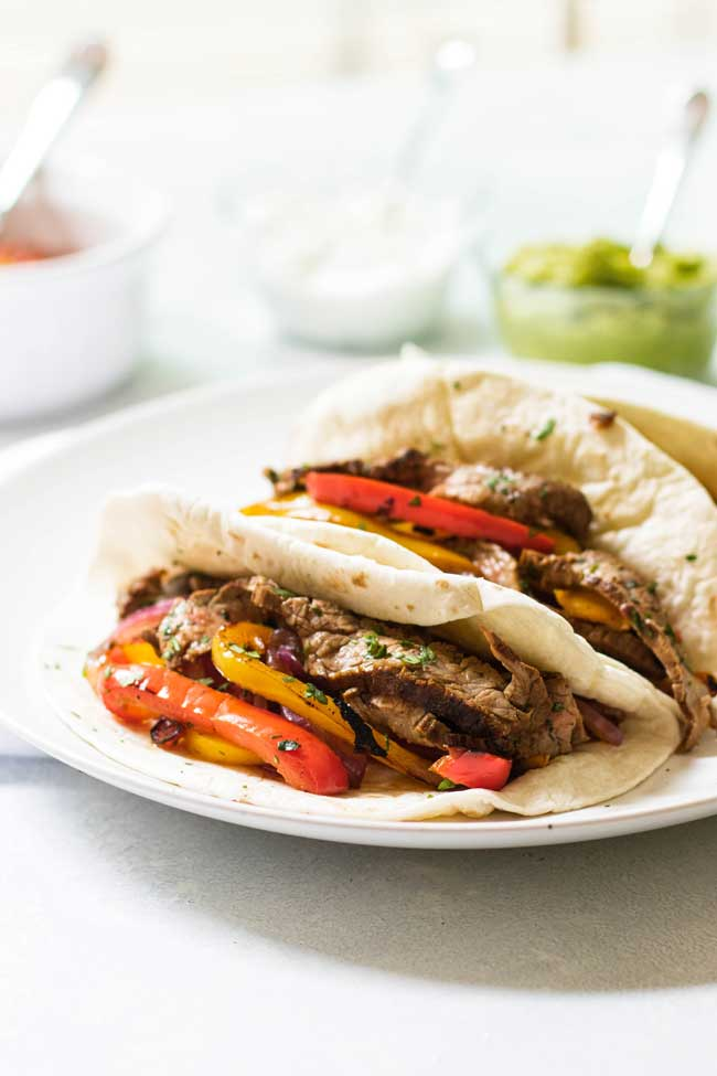 Beef Fajitas on a white plate with guacamole in the background