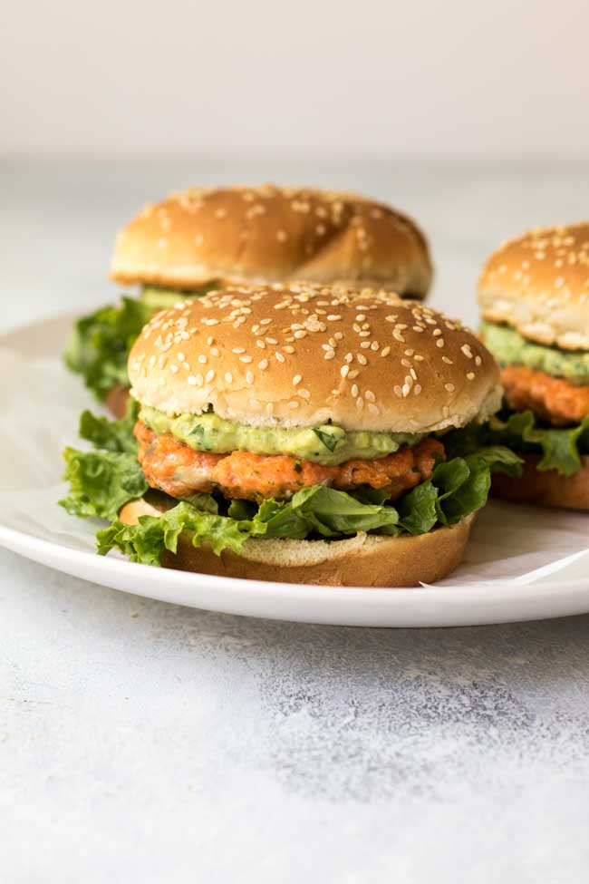 Cilantro-lime salmon burgers with avocado mayo on a white plate