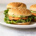 Salmon burgers with avocado mayo on a plate