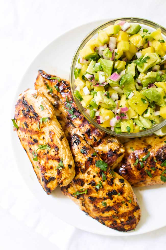 overhead photo of grilled chicken with a bowl of mango avocado salsa
