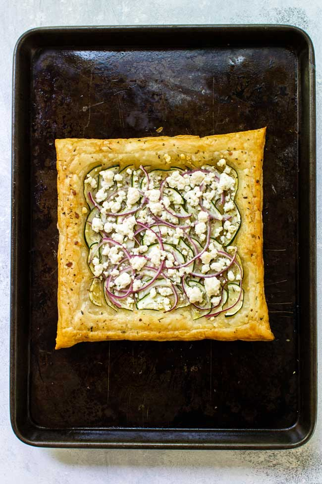 zucchini and goat cheese puff pastry on a baking sheet