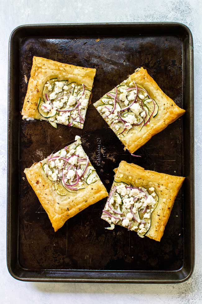 zucchini and goat cheese puff pastry tart cut into four pieces