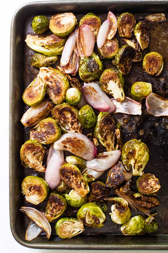 Roasted brussels sprouts and shallots on a baking sheet