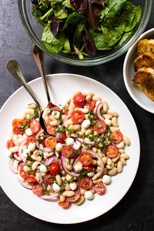 White Bean Tomato Salad on a white plate with a bowl of lettuce and bread on the side
