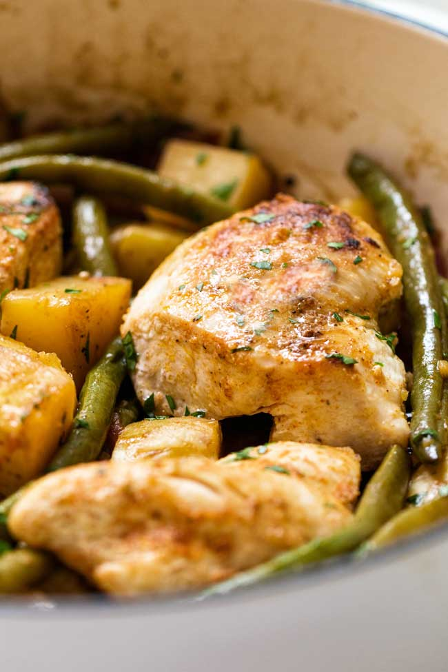 close-up photo of a piece of chicken in a pan with green beans and potatoes