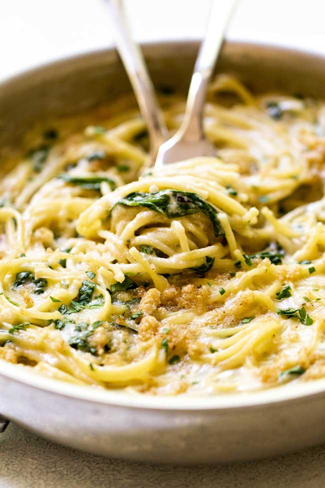 Creamy Gruyere Spaghetti with breadcrumbs and spinach in a skillet