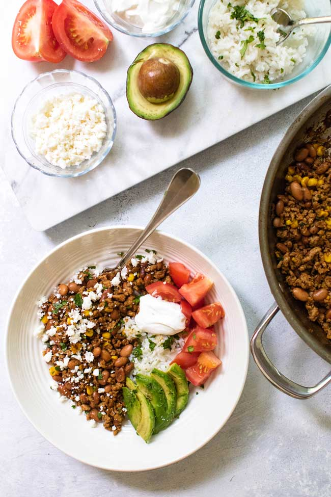 ground turkey taco bowl with tomatoes, avocado, cheese, and rice