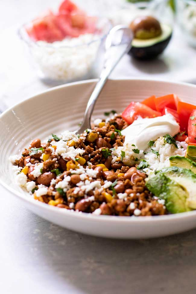 ground turkey taco bowl with cheese and an avocado