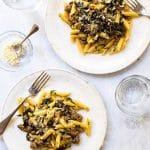 One-pot pasta with sausage and arugula on two plates