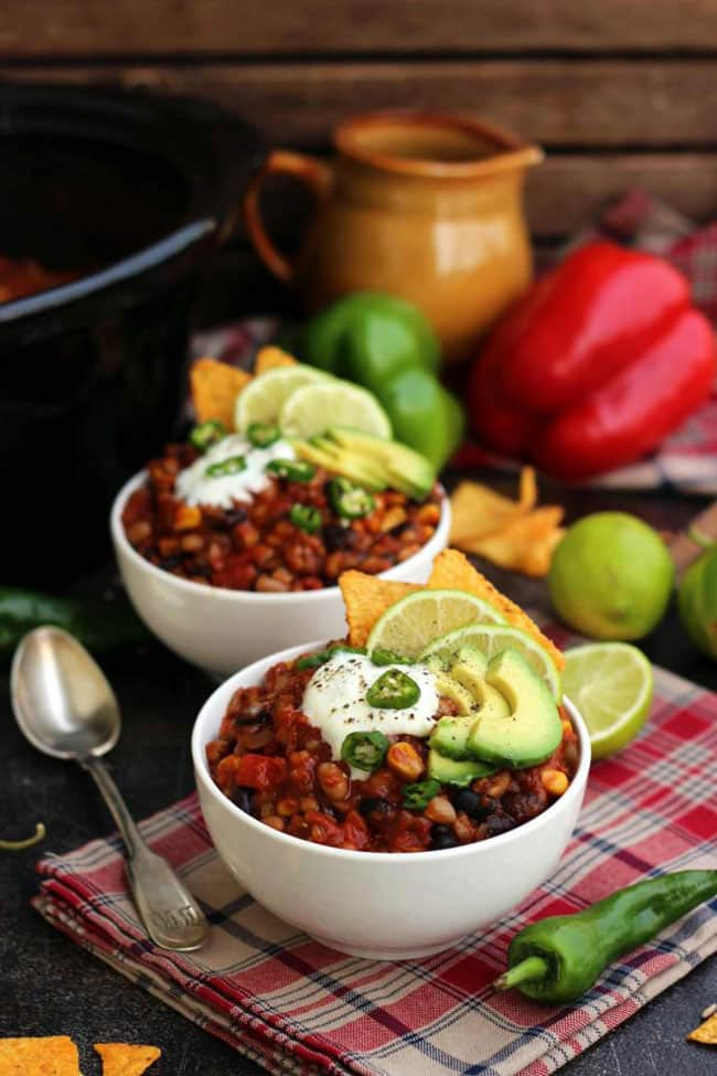 Two bowls of slow cooker vegan chili topped with sour cream
