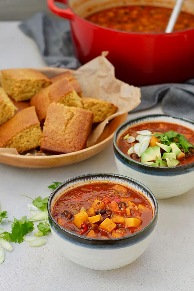 Two bowls of butternut squash black bean chili with cornbread