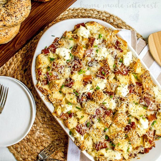 A breakfast casserole in a baking dish made with everything bagels, bacon, eggs, and cheese.
