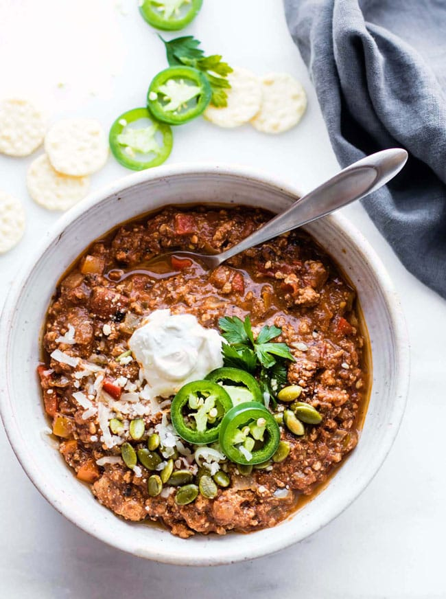 A bowl, with a spoon, of quick sweet potato mole turkey chili topped with herbs and sour cream