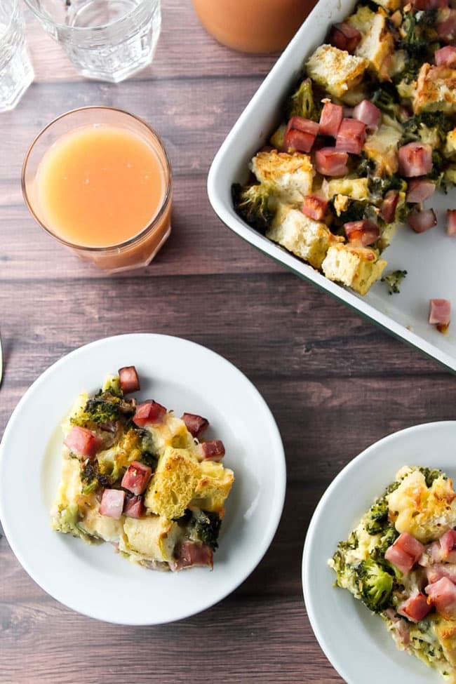 Ham and Broccoli Strata in a baking dish with slices of the casserole on white plates with glasses of grapefruit juice and water nearby.