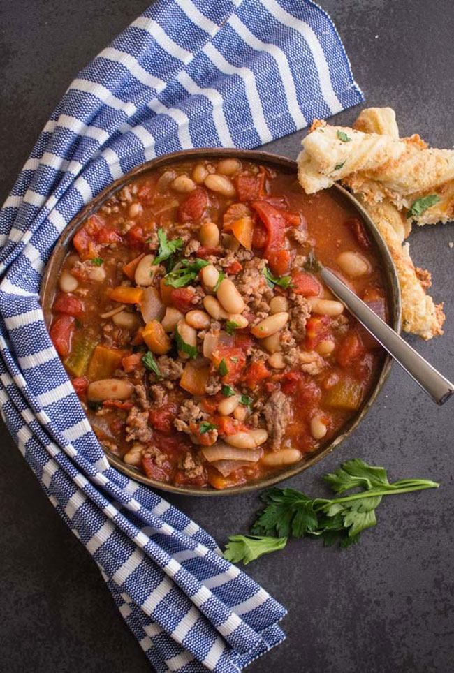 A big bowl of chili with beans with a napkin wrapped around the bowl