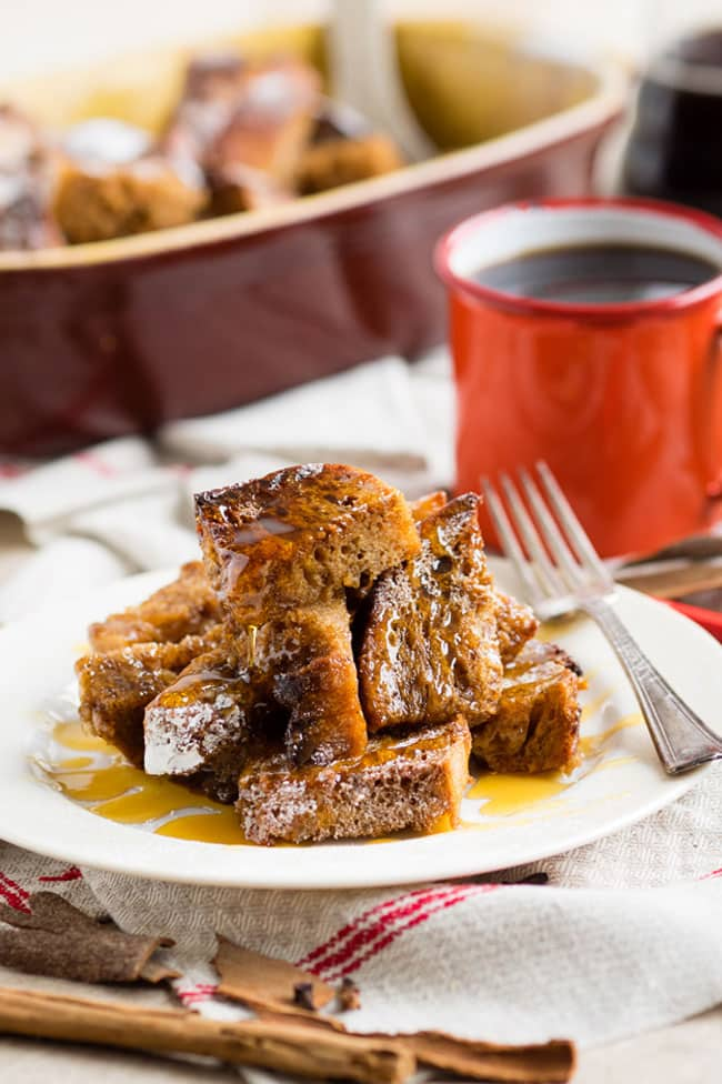 One serving of baked gingerbread French toast on a plate with syrup and a fork. A cup of coffee and the baking dish in the background.