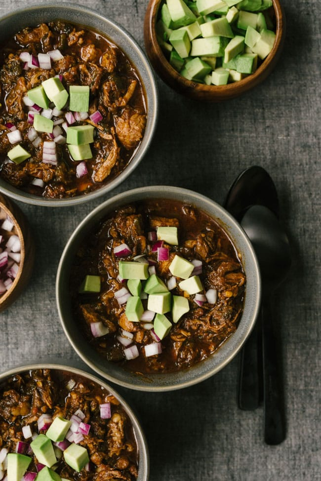 Overhead shot of three bowls of paleo chili con carne topped with diced avocaod