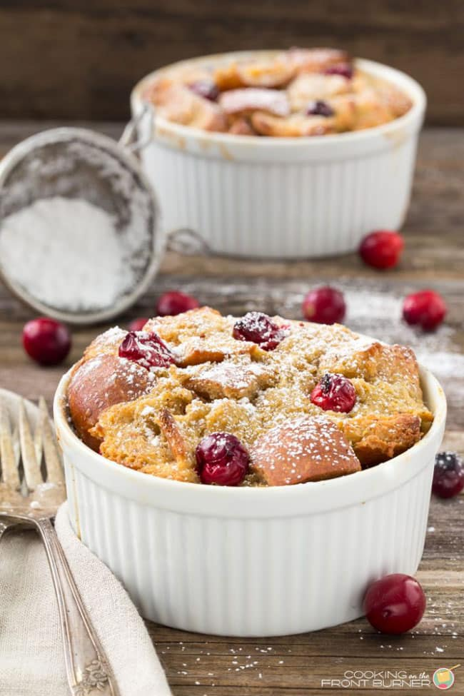 Two Overnight Eggnog Cranberry French Toast servings in individual white ramekins dusted with powdered sugar with some cranberries scattered around and powdered sugar in a sieve in the background.