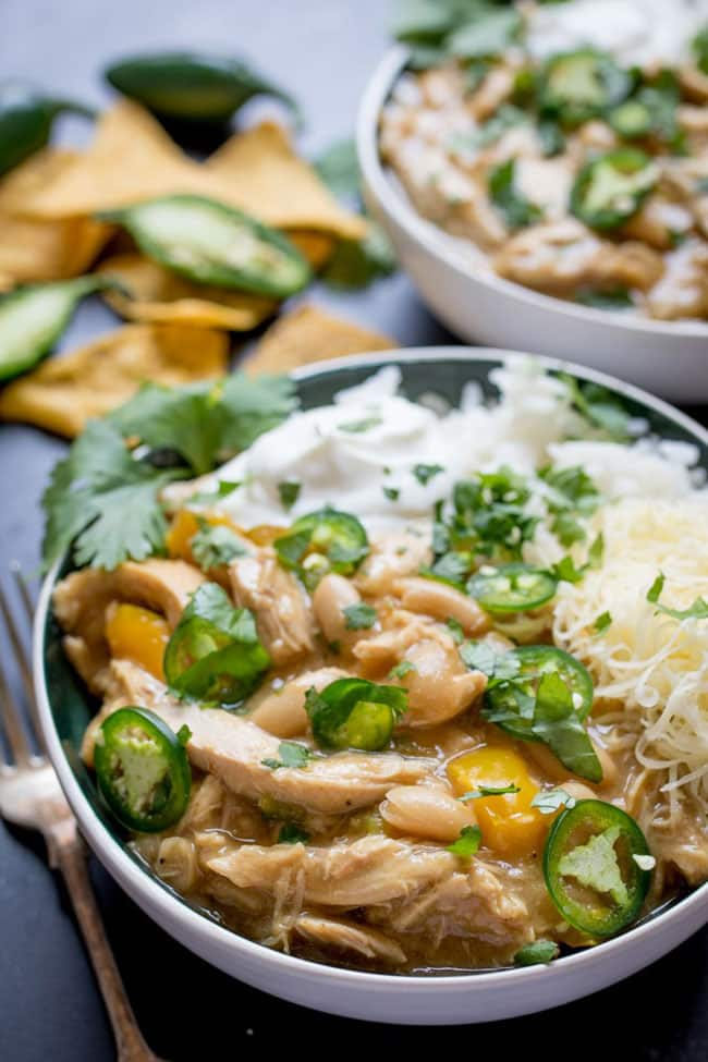 A bowl of white chicken chili topped with jalapeno peppers