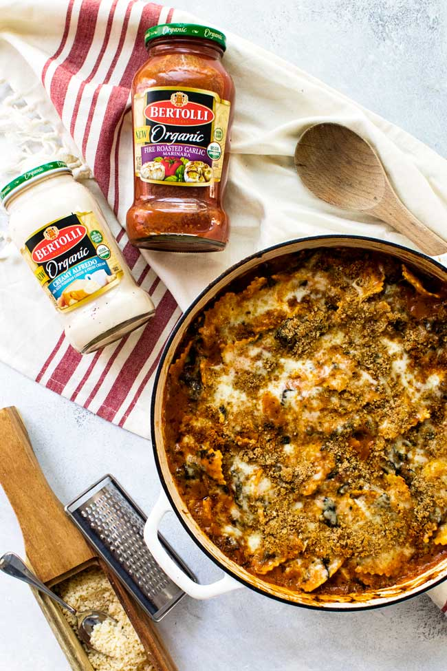 Pan with baked ravioli in spinach rosa sauce with bottles of bertolli sauces, grated parmesan cheese, and a wooden spoon