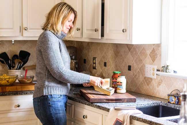 Woman standing at counter grating parmesan