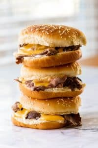 A stack of three hot roast beef sandwiches with cheddar cheese sauce