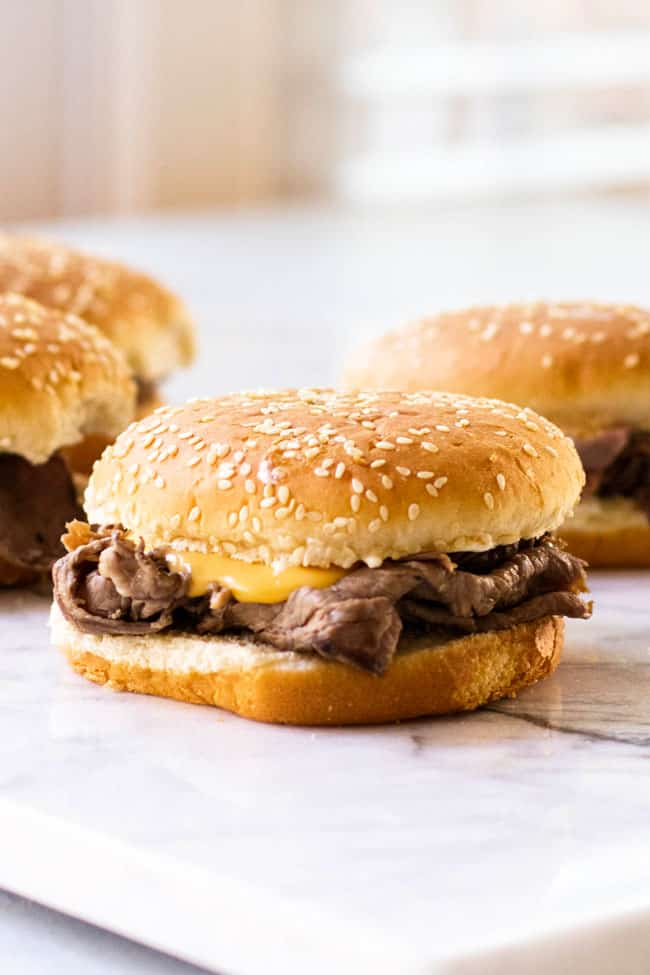 Hot roast beef on a sesame hamburger bun with cheddar cheese sauce