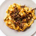 Pappardelle pasta on a gray plate topped with braised short rib muchroom sauce