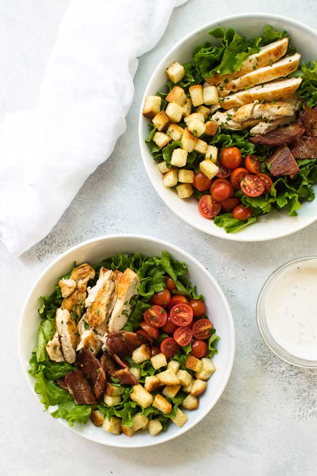 Two bowls with lettuce, cooked chicken, tomatoes, bacon, homemade croutons and lettuce with dressing in a small bowl on the side