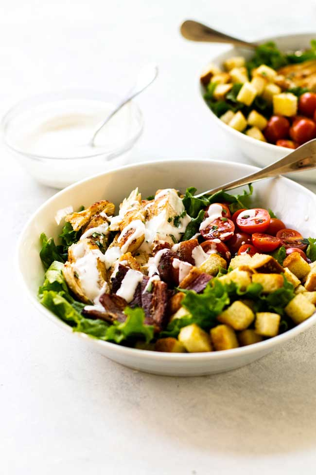 A bowl of Chicken BLT salad with some yogurt-mayo dressing drizzled over the top.