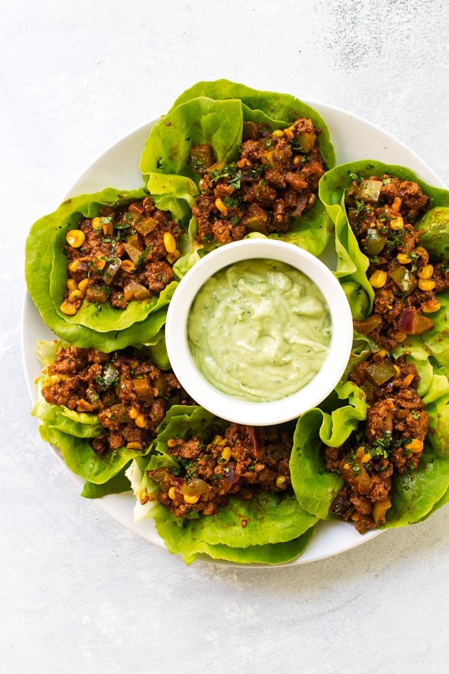 Chipotle beef lettuce wraps on a white plate with a bowl of avocado sauce in the middle
