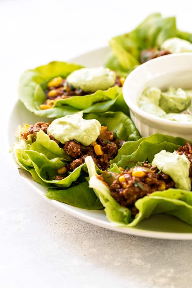 Chipotle beef lettuce wraps with dollops of creamy avocado sauce