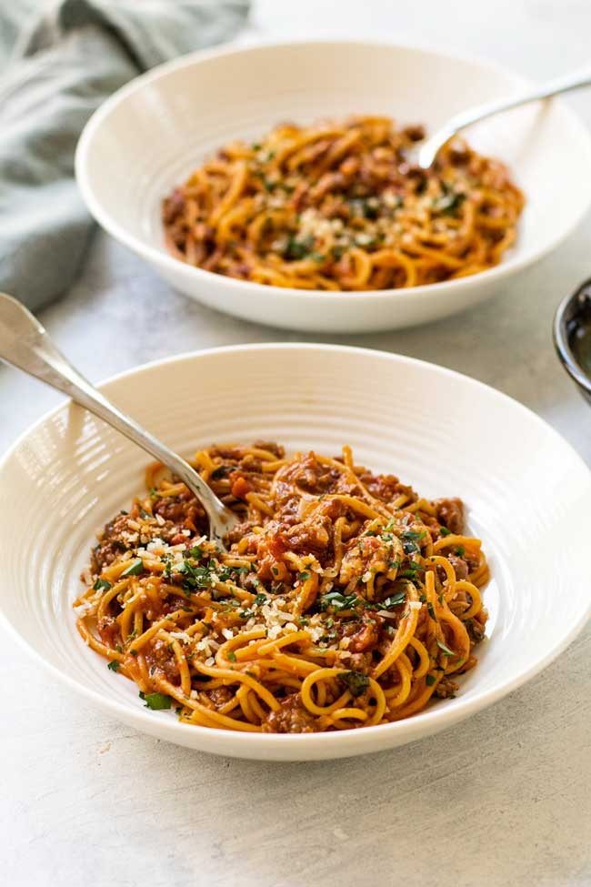 Two bowls of spaghetti bolognese with sun-dried tomatoes
