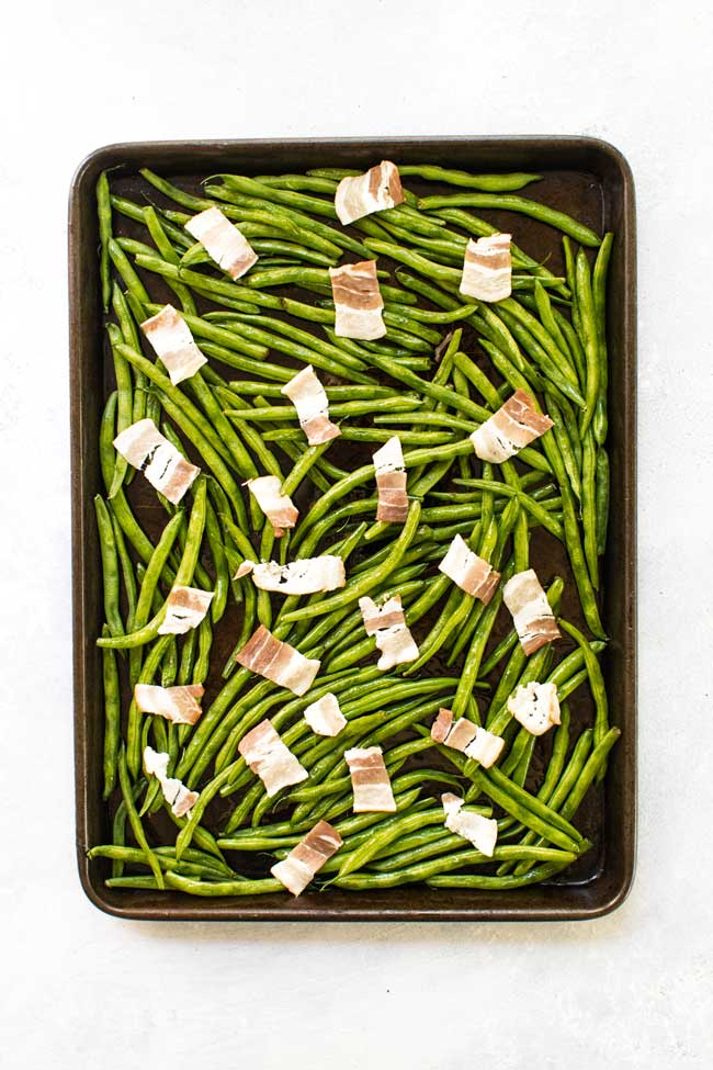 Fresh green beans and bacon on a baking sheet ready to go in the oven
