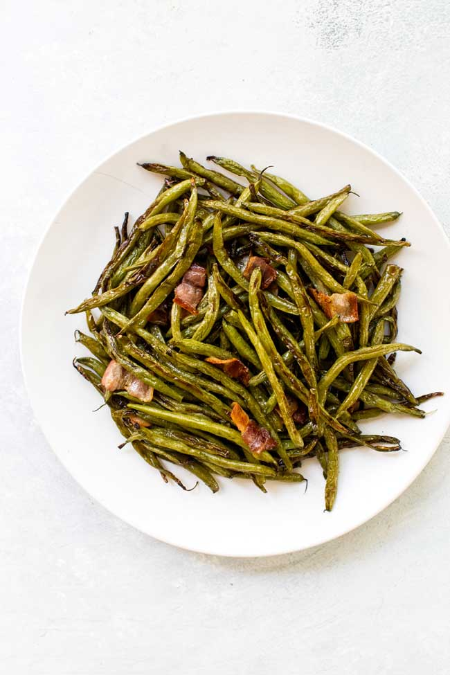 Roasted green beans on a white plate