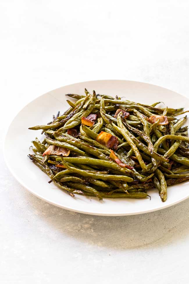 Roasted green beans with bacon tossed with a dill vinaigrette. Served on a white plate.