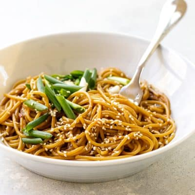 Sesame noodles topped with green onions in a bowl with a fork