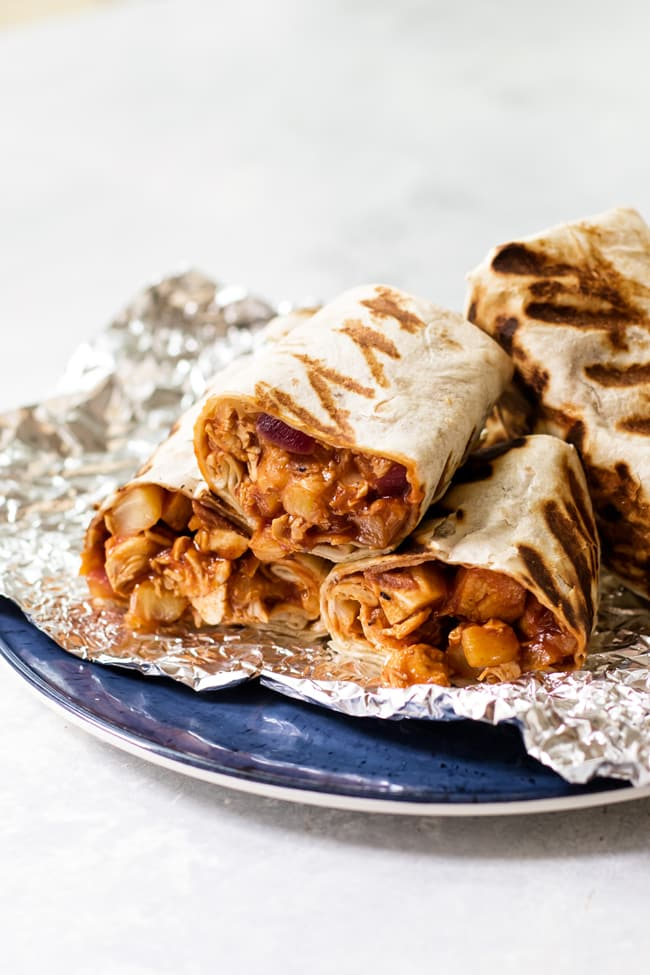 Tropical BBQ chicken wraps sliced in half on some tin foil that is on a blue plate