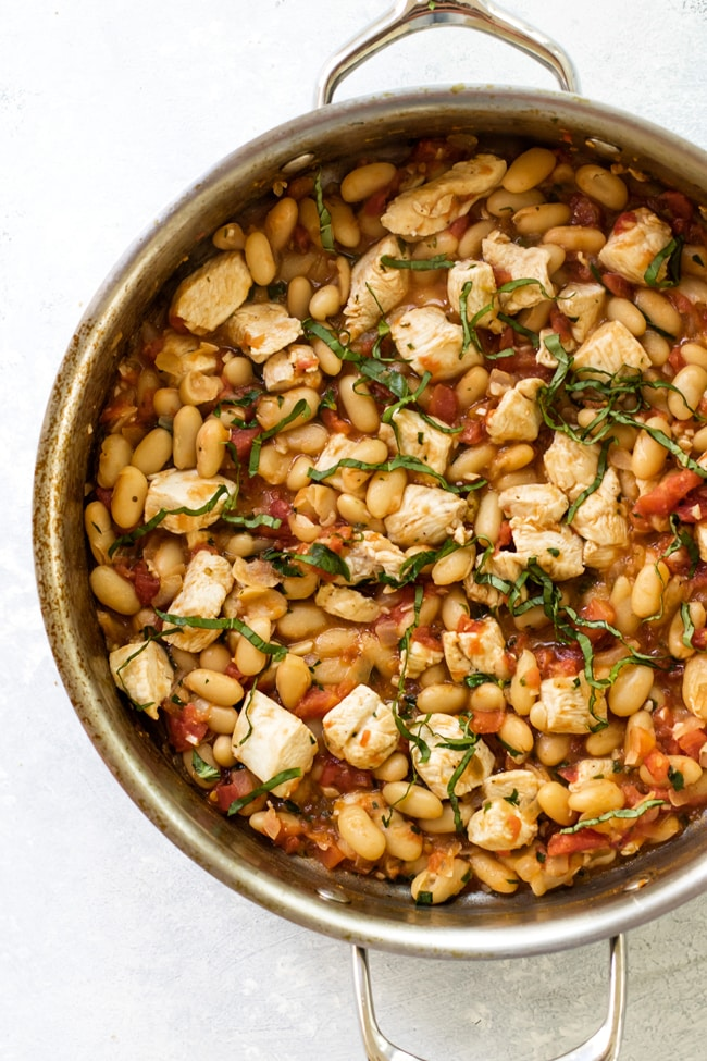 A large skillet with tuscan-style chicken made with white wine, diced tomatoes, white beans and fresh herbs