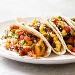 four breakfast tacos on a plate