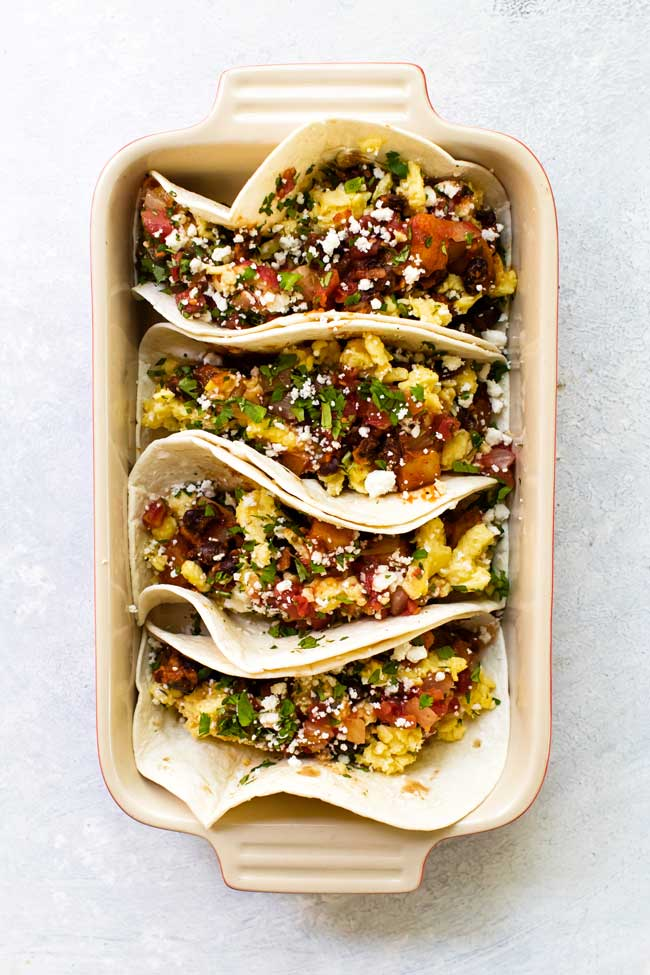 Breakfast tacos lined up in a baking dish for serving