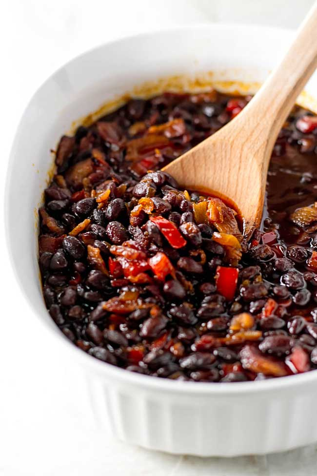 baked black beans in a white dish with a wooden spoon
