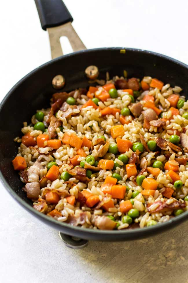bacon fried rice with peas and carrots in a skillet