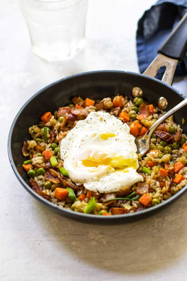 bacon fried rice in a black skillet with an egg on top