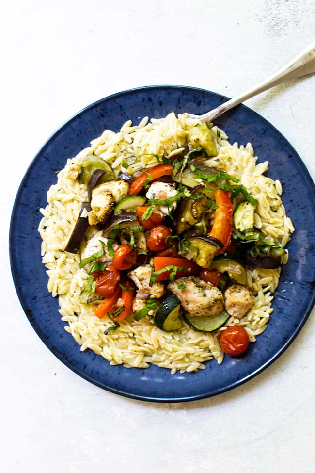 one serving of sheet pan chicken ratatouille on a blue plate with butter herb orzo