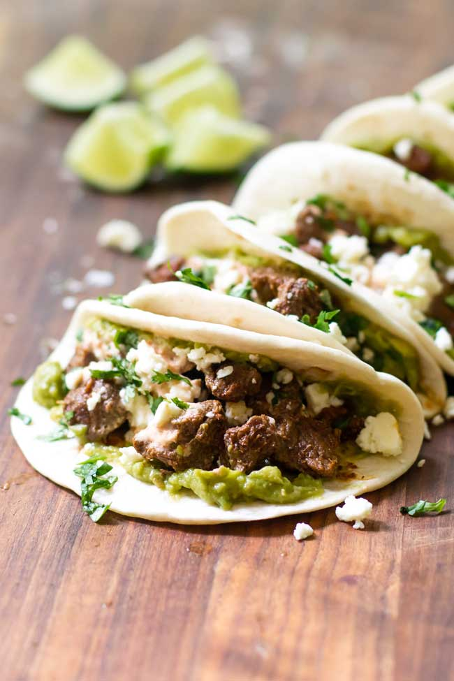 beef tacos on a cutting board with lime wedges