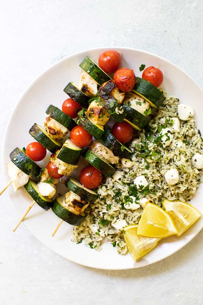chicken kabobs on a white plate with pesto rice and lemon wedges