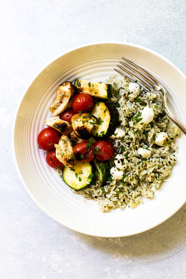a bowl of chicken, tomatoes, and zucchini with pesto rice